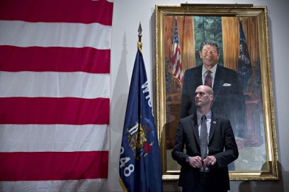 """A security guard stands near a portrait of former U.S. President Ronald Reagan as Senator Ted Cruz, a Republican from Texas and 2016 presidential candidate, not pictured, speaks during the """"Wisconsin Decides 2016"""" hosted by Republican Party of Milwaukee in Milwaukee, Wisconsin, on Friday, April 1, 2016. After months of tense dealings with Republican presidential front-runner Donald Trump, the Republican National Committee's biggest challenge is beginning to take shape: how to navigate a scenario in which Trump leads his challengers in votes and delegates heading into the convention, but loses the nomination. Photographer: Daniel Acker/Bloomberg"""